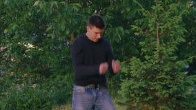 Hoppar praktiserande parkour för den unga mannen i parkera långsamt arkivfilmer