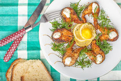 Сhopped pieces of fried fish on a tablecloth Royalty Free Stock Photo