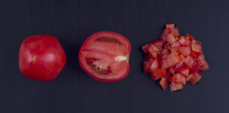 Сhopped tomatoes on a black background Stock Photos