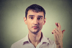 Hoppfull stilig man för stående som korsar hans fingrar som hoppas, fråga som är bästa Royaltyfri Foto