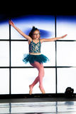 Hopping Ballerina. A young girl performs ballet on stage in a performance rehearsal. She is doing a leap Royalty Free Stock Photography