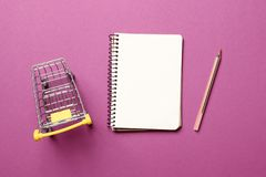 Hopping cart, blank paper notebook with pen on a pink background. Shopping concept. shopping cart, blank paper notebook with pen on a pink background royalty free stock photo