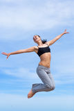 Hopping girl. Barefoot young woman in short tank top and sporting trousers jumps against the sky Royalty Free Stock Photography