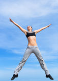 Hopping girl. Young woman in short tank top and sporting trousers jumps against the sky Royalty Free Stock Photo
