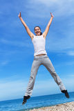 Hopping girl. Young woman in white blouse and sporting trousers jumps against the sky Stock Images