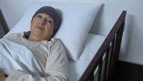 Hopplös kvinnlig patient som lider cancer som ligger i sjuksäng och ser kameran lager videofilmer