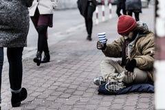 Hopplös tiggare på trottoaren royaltyfri bild