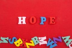 HOPPord på röd bakgrund som komponeras från träbokstäver för färgrikt abc-alfabetkvarter, kopieringsutrymme för annonstext lära Arkivbilder