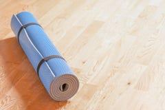 Hoprullad blå yoga som är matt på golvet arkivfoto