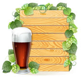 Hops branch and beer glass on a wooden background Stock Image