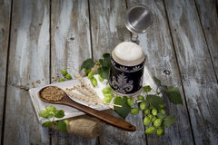 Hops and malt seeds and spikes traditional beer jug on cloth napkin Stock Image