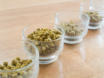 Hops pellets in glass cup for brewing beer Stock Photo
