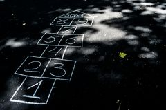 Hopscotch που επισύρεται την προσοχή με την κιμωλία στη μαύρη άσφαλτο ελεύθερη απεικόνιση δικαιώματος