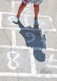Hopscotch. A child playing Hopscotch in a playground Stock Image