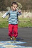Παιδί που πηδά hopscotch Στοκ Εικόνες