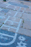 Hopscotch on an asphalt floor with chalk drawings of numbers and Royalty Free Stock Images