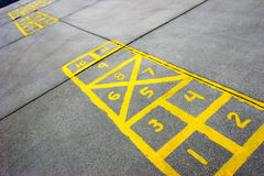 Hopscotch board at schoolyard. Yellow hopscotch boards painted on cement at a schoolyard Stock Photo