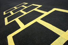 Hopscotch game yellow on pavement. Hopscotch jumping game at a school, yellow on black stock images