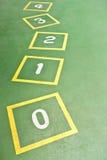 Hopscotch giallo sul campo da giuoco verde fotografia stock libera da diritti