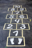 Hopscotch painted indelible ink on black asphalt Stock Photography