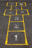 Hopscotch popular street game in schoolyard pavement. Stock Photos