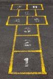Hopscotch popular street game in schoolyard pavement. Stock Photos