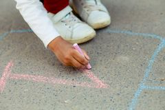 Hopscotch in a schoolyard on an asphalt floor with chalk drawings of numbers and squares as an icon of youth innocence. Hopscotch in a schoolyard on an asphalt Royalty Free Stock Images