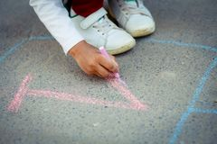 Hopscotch in a schoolyard on an asphalt floor with chalk drawings of numbers and squares as an icon of youth innocence. Hopscotch in a schoolyard on an asphalt Royalty Free Stock Photo