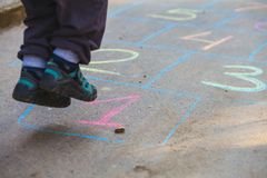 Hopscotch in a schoolyard on an asphalt floor with chalk drawings of numbers and squares as an icon of youth innocence. Hopscotch in a schoolyard on an asphalt Stock Image