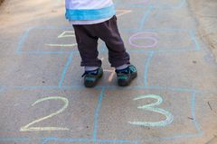 Hopscotch in a schoolyard on an asphalt floor with chalk drawings of numbers and squares as an icon of youth innocence. Hopscotch in a schoolyard on an asphalt Stock Photo
