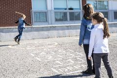 Hopscotch on the schoolyard with friends play together Stock Photo