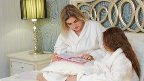 Hora de acostarse de la hija de la lectura de la familia del cuidado del amor de madre almacen de video
