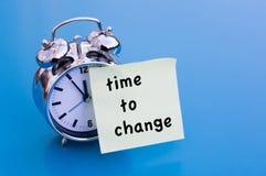 Hora de cambiar en el papel con el despertador Fotos de archivo
