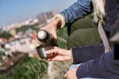 Hora de descansar e aquecer-se Close-up de pares novos com garrafa térmica fotos de stock royalty free