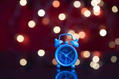 Hora de despertar para trabajar, despertador azul con la decoración del partido Imágenes de archivo libres de regalías
