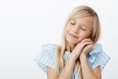 Hora de dormir Pequeña muchacha europea linda soñolienta con el pelo rubio, los ojos de cierre e inclinarse en las palmas como si imágenes de archivo libres de regalías