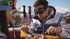 Hora de la almuerzo en una estación de esquí Pares jovenes que almuerzan en restaurante al aire libre en las montañas y comunicar almacen de metraje de vídeo