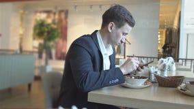 Hora de la almuerzo Hombre hermoso con un teléfono en un café almacen de video