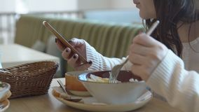Hora de la almuerzo Mujer joven en café con el teléfono metrajes