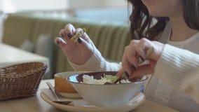 Hora de la almuerzo Una mujer joven come en un café almacen de video