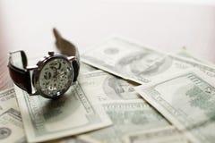 Hora de pagar - 100 dólares de billete de banco y el reloj clásico con los números romanos fotos de archivo libres de regalías