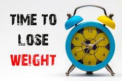 Hora de perder o peso em um fundo branco Despertador retro imagem de stock