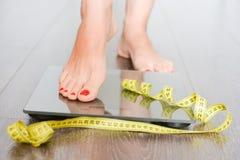 Hora de perder quilogramas com os pés da mulher que pisam em uma escala do peso foto de stock royalty free