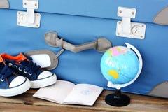 Hora de prepararse para el día de fiesta con la maleta, el pasaporte, las zapatillas de deporte y el globo retros en concepto del Foto de archivo
