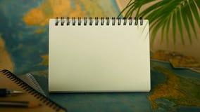 Hora de viajar concepto Tema tropical de las vacaciones con el mapa del mundo y el cuaderno Artículos del viaje con el espacio de almacen de metraje de vídeo