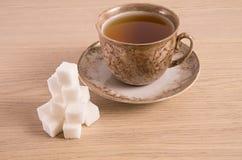 Hora do copo de Brown com os cubos do açúcar em um fundo claro Fotografia de Stock Royalty Free