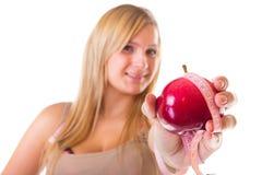 Hora para adelgazar de la dieta. Mujer con la manzana y la cinta métrica Fotografía de archivo