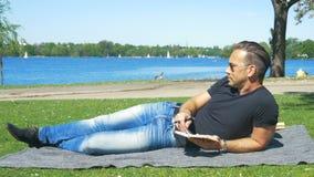 Hora para a autorreflexão - um homem relaxa no fim de semana no parque da cidade filme