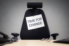 A hora para a cadeira vazia do negócio da mudança com assina dentro o escritório imagem de stock