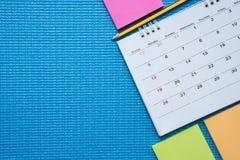 Hora para ejercitar, calendario en el fondo azul de la estera de la yoga Imagen de archivo